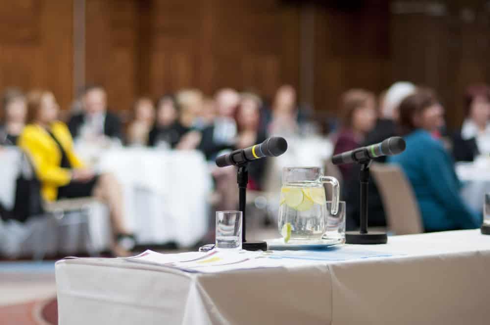 Detalle de mesa con micrófono en sala de conferencias